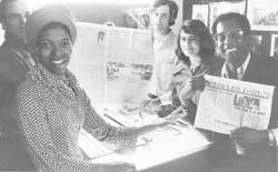 Peoples Temple staff members holding the first large format, newsprint issue of Peoples Forum in December 1976. Left to right: Tim Carter, Frances Johnson, Tim Clancey, Gloria Rodriguez (Carter), Jim Ingram.