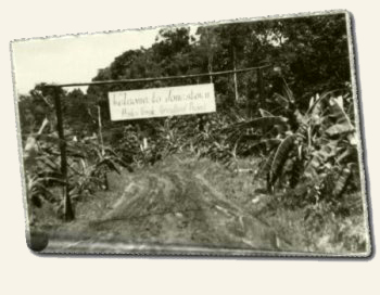 "The sign reads: ""Welcome to Jonestown, Peoples Temple Agricultural Project"""